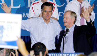 **FILE** Golf legend Jack Nicklaus (right) welcomes Republican presidential candidate Mitt Romney to the stage during a campaign rally on Sept. 26, 2012, in Westerville, Ohio. (Associated Press)