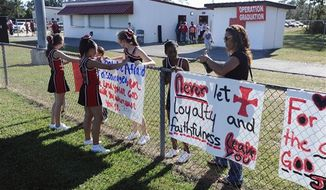** FILE ** The cheerleaders of Kountze Middle School use their faith-based signs at the middle school football game held at Kountze High School on Thursday, Sept. 20, 2012, in Kountze, Texas. (AP Photo/The Beaumont Enterprise, Randy Edwards)