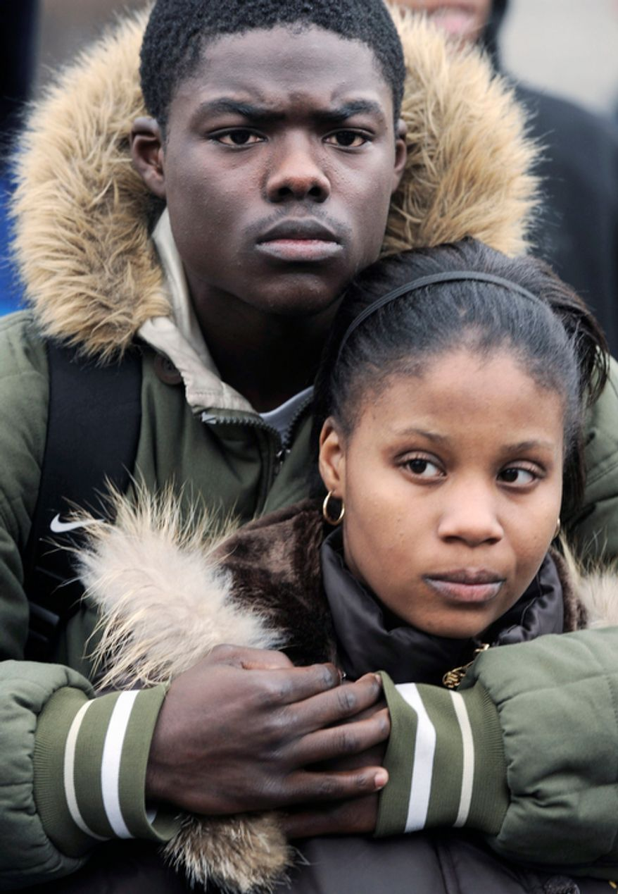 In a March 10, 2008 file photo, Crane Tech High School students Corey Woods and Brittney Waters comfort each other at the school during a memorial for student Ruben Ivy, 18, who was killed outside the Chicago school March 7. Officials initiated a program to escort students to and from a nearby public housing complex after more than 100 simply stopped coming to class for fear of retaliation after a reputed gang member from the complex shot and killed Ivy. (AP Photo/Paul Beaty, File)