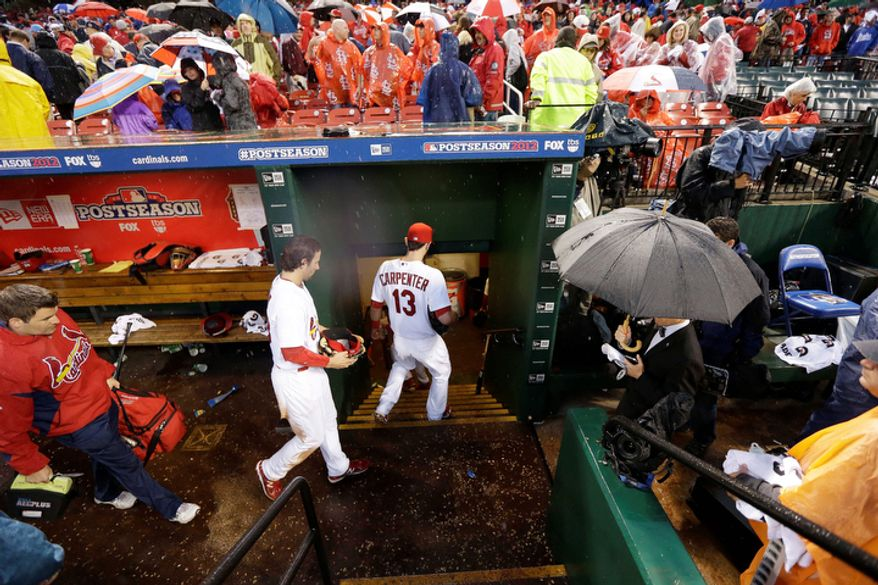 St. Louis Cardinals players leave the dugout during a rain delay of Game 3 of baseball's National League championship series against the San Francisco Giants, Wednesday, Oct. 17, 2012, in St. Louis. (AP Photo/David J. Phillip)