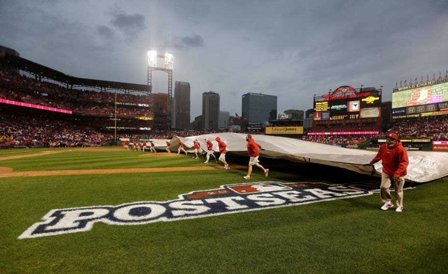 5Ground crew covers the field during a rain delay of Game 3 of baseball's National League championship series between the St. Louis Cardinals and San Francisco Giants, Wednesday, Oct. 17, 2012, in St. Louis. (AP Photo/David J. Phillip)