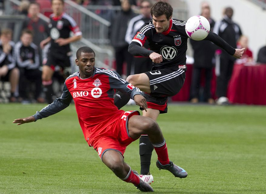 Toronto FC 's Aaron Maund, left, blocks a shot from D.C United's Chris Pontius during first half MLS action in Toronto on Saturday, Oct. 6, 2012. (AP Photo/The Canadian Press, Chris Young)