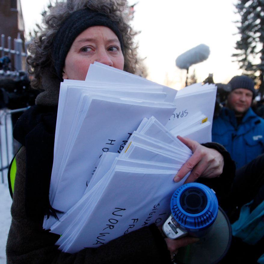 "A representative of Amnesty International holds petitions signed by 100,000 people around the world to demand the freedom of Nobel peace laureate Liu Xiaobo Thursday Dec. 9, 2010 outside te Chinese Embassy in Oslo, Norway. A day before the Nobel committee honors Liu, an imprisoned Chinese dissident with its peace prize, China ratched up the rhetoric calling the award ""an interference"" in its internal affairs. (AP Photo/John McConnico)"