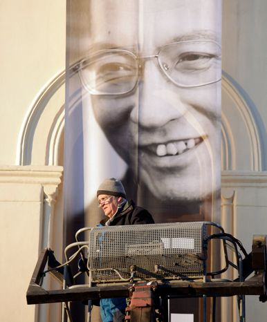 "A worker installs a banner outside the Nobel Peace Center for Nobel peace laureate Liu Xiaobo Thursday Dec. 9, 2010 in Oslo, Norway. A day before the Nobel committee honors Liu, an imprisoned Chinese dissident with its peace prize, China ratched up the rhetoric calling the award ""an interference"" in its internal affairs. The exhibit is called ""I Have No Enemies."" (AP Photo/John McConnico)"