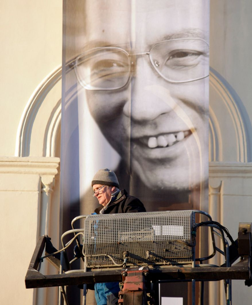 """A worker installs a banner outside the Nobel Peace Center for Nobel peace laureate Liu Xiaobo Thursday Dec. 9, 2010 in Oslo, Norway. A day before the Nobel committee honors Liu, an imprisoned Chinese dissident with its peace prize, China ratched up the rhetoric calling the award """"an interference"""" in its internal affairs. The exhibit is called """"I Have No Enemies."""" (AP Photo/John McConnico)"""