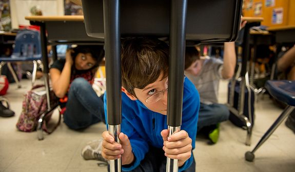 Left to right: Seventh graders Ambika Minocha, 12, Alex Letchworth, 12, and Scott Browoning, 13, and their fellow classmates at Langston Hughes Middle School drop under their desk and hold on as they participate in the Great ShakeOut national earthquake drill, Reston, Va., Thursday, October 18, 2012. Students in the Washington, D.C. region are now participating in the earthquake preparation program for the first time after a 5.8 magnitude earthquake struck the area in August 2011. According to the program's website, an estimated 18 million people are participating this year. (Andrew Harnik/The Washington Times)