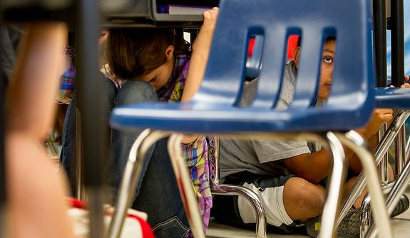 Seventh grader Miguel Ortega, 12, right, and his fellow classmates at Langston Hughes Middle School drop under their desk and hold on as they participate in the Great ShakeOut national earthquake drill, Reston, Va., Thursday, October 18, 2012. Students in the Washington, D.C. region are now participating in the earthquake preparation program for the first time after a 5.8 magnitude earthquake struck the area in August 2011. According to the program's website, an estimated 18 million people are participating this year. (Andrew Harnik/The Washington Times)