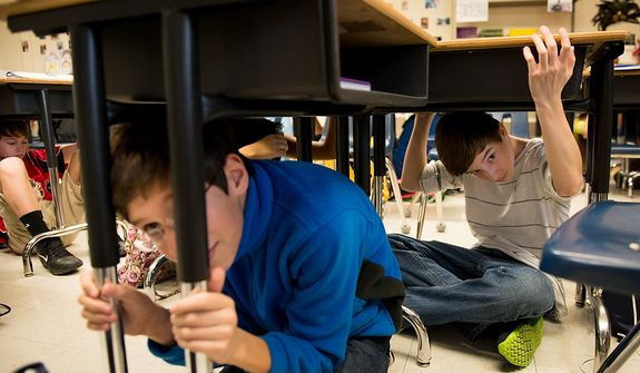 Left to right: Seventh graders Jack Dooley, 12, Alex Letchworth, 12, and Scott Browoning, 13, and their fellow classmates at Langston Hughes Middle School drop under their desk and hold on as they participate in the Great ShakeOut national earthquake drill, Reston, Va., Thursday, October 18, 2012. Students in the Washington, D.C. region are now participating in the earthquake preparation program for the first time after a 5.8 magnitude earthquake struck the area in August 2011. According to the program's website, an estimated 18 million people are participating this year. (Andrew Harnik/The Washington Times)
