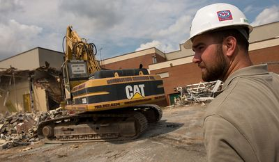 Assistant project manager Brandon Chambers watches as demolition begins on Louisa County High School two days before the one year anniversary of the magnitude 5.8 earthquake that hit near Mineral, Va., causing millions of dollars worth of damage and was felt in nearly every state along the east coast, Mineral, Va., Tuesday, August 21, 2012. The school sustained massive structural damage and was deemed unsafe, forcing all their students to move into nearby trailers. (Andrew Harnik/The Washington Times)