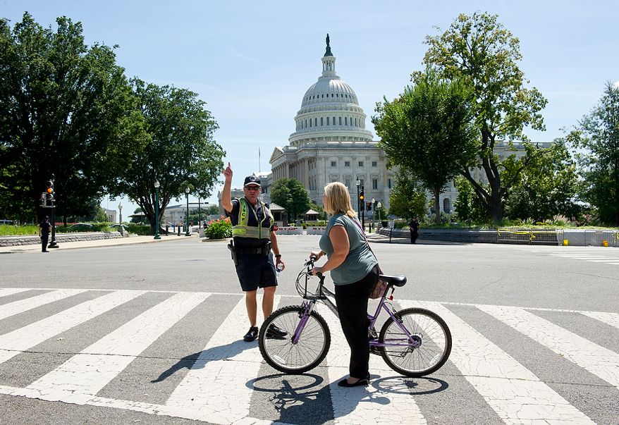 A U.S. Capitol Police officer directs a cyclist away from the Capitol building on Tuesday, Aug. 23, 2011. All buildings downtown are evacuated Tuesday following a 5.9 earthquake whose epicenter was in Mineral, Va., east of Charlottesville, but whose effects could be felt up the entire Eastern seaboard, including Washington, D.C. (Barbara L. Salisbury/The Washington Times)