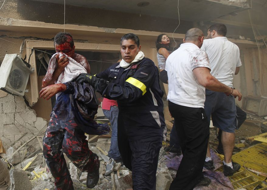 A Lebanese rescue worker (center) helps an injured man at the scene of an car bomb explosion Oct. 19, 2012, in the mostly Christian neighborhood of Achrafiyeh in Beirut. (Associated Press)