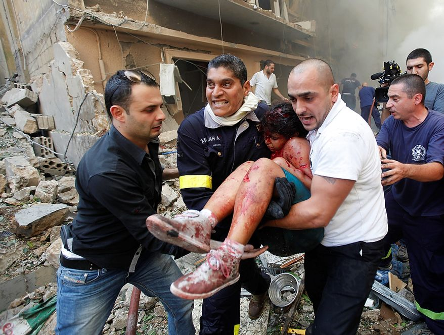 Lebanese rescue workers and civilians carry an injured girl from the scene of a car bomb explosion in the mostly Christian neighborhood of Achrafiyeh in Beirut on Oct. 19, 2012. The bomb killed at least eight people and wounded dozens in the worst blast the city has seen in years, officials said. (Associated Press)