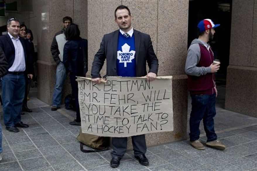 Toronto Maple Leafs fan Barry Murphy waits for the arrival of NHL commissioner Gary Bettman outside the offices of the NHLPA ahead of the continuation of collective bargaining talks in Toronto on Thursday, Oct. 18, 2012. (AP Photo/The Canadian Press, Chris Young)