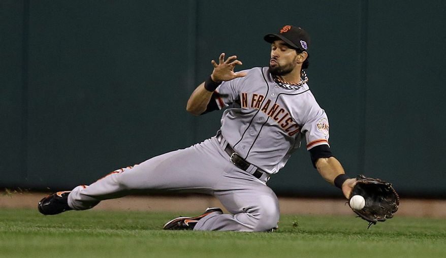 San Francisco Giants' Angel Pagan can't handle a run-scoring hit by St. Louis Cardinals' Matt Holliday in the fifth inning of Game 4 of the National League Championship Series on Oct. 18, 2012, in St. Louis. (Associated Press)