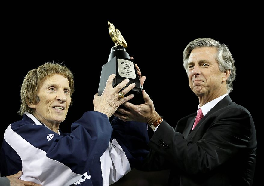 Detroit Tigers owner Mike Ilitch (left) and general manager Dave Dombrowski lift the William Harridge Trophy after at Game 4 of the American League Championship Series against the New York Yankees in Detroit. The Tigers won, 8-1, to sweep the Yankees and move on to the World Series. (AP Photo/Matt Slocum)