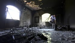 ** FILE ** A Libyan man investigates the inside of the U.S. Consulate in Benghazi, Libya, on Sept. 13, 2012, after an attack two days earlier that killed four Americans, including Ambassador J. Christopher Stevens. (Associated Press)
