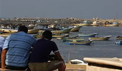 ** FILE ** Palestinians sit by the port in Gaza City, Wednesday, Oct. 17, 2012. (AP Photo/Adel Hana)