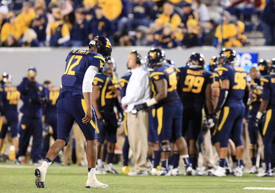 West Virginia quarterback Geno Smith and the Mountaineers absorbed their worst defeat in Morgantown since a 58-14 loss to Miami in 1986. (Associated Press)