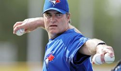 FILE - In this April 1, 2012, file photo, Toronto Blue Jays manager John Farrell throws batting practice before the Blue Jays' spring training baseball game against the Pittsburgh Pirates in Dunedin, Fla. The Boston Red Sox reportedly have reached an agreement to bring Farrell to Boston to replace Bobby Valentine. Red Sox spokeswoman Pam Kenn said early Sunday, Oct. 21, 2012, the team had no announcement to make. Comcast SportsNet New England reported that the deal was agreed to. (AP Photo/Kathy Willens, File)