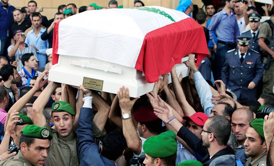 Honor guards carry the coffin, which is wrapped in the Lebanese flag, of Brig. Gen. Wissam al-Hassan during the funeral procession at Martyrs Square in Beirut on Sunday. Gen. al-Hassan was killed by a car bomb on Friday. (Associated Press)