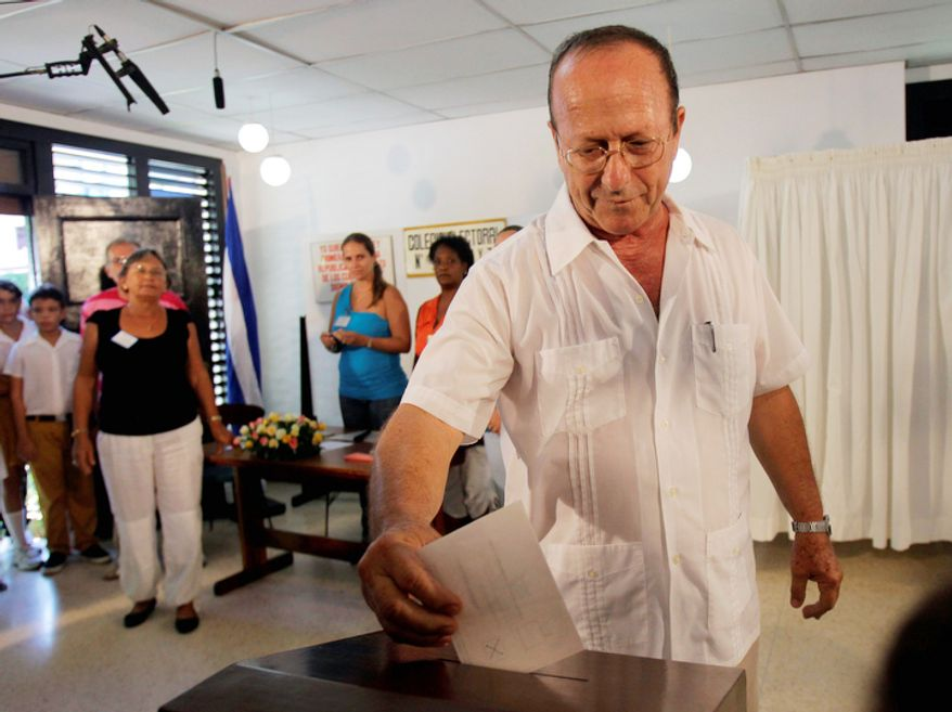 Santiago Gonzalez Guerra, center, a member of the Electoral Board, casts Cuba's leader Fidel Castro's ballot in his name in Havana, Sunday Oct. 21, 2012. Cubans are going to the polls Sunday to vote in municipal elections. (AP Photo/Ismael Francisco/Cubadebate)