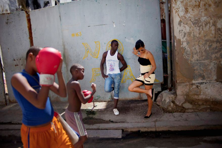 A woman and man stand on the sidewalk as kids sharing a pair of boxing gloves walk home as they practice punches after working out at a gym in Old Havana, Cuba, Saturday, Oct. 20, 2012.  On Sunday, Cubans will cast ballots to choose among candidates for municipal assemblies that administer local governments and relay complaints on issues such as potholes and housing, social and sports programs. (AP Photo/Ramon Espinosa)