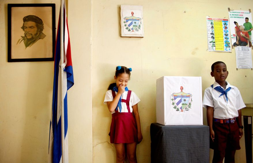 "Cuban school children wait for voters during municipal elections next to a picture of the late revolutionary hero Ernesto ""Che"" Guevara in a polling station in Havana Sunday Oct. 21, 2012.  Cuban school children known as ""pioneros"" are in all polling stations during elections overseeing the process.(AP Photo/Ramon Espinosa)"