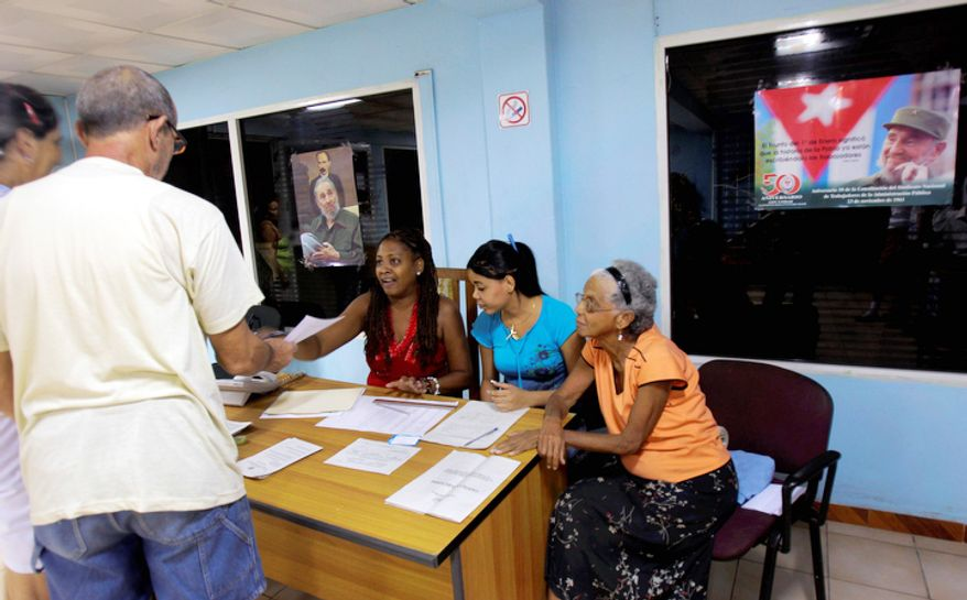 Under pictures of Cuba's leader Fidel Castro, people cast their ballots at a polling station in Havana, Sunday Oct. 21, 2012. Cubans are going to the polls Sunday to vote in municipal elections.  (AP Photo/Ismael Francisco/Cubadebate)