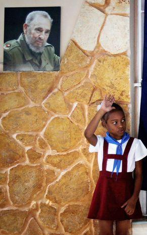 """Under a picture of Cuba's leader Fidel Castro, a Cuban schoolgirl raises her hand confirming a voter is casting his ballot properly during municipal elections in Havana Sunday Oct. 21, 2012.  Cuban school children known as """"pioneros"""" are in all polling stations during elections overseeing the process.  A top executive of the Hotel Nacional told the AP Sunday 86-year-old Fidel Castro appeared in public for the first time in months at the hotel Saturday challenging persistent rumors that the aging revolutionary is near death. (AP Photo/Franklin Reyes)"""