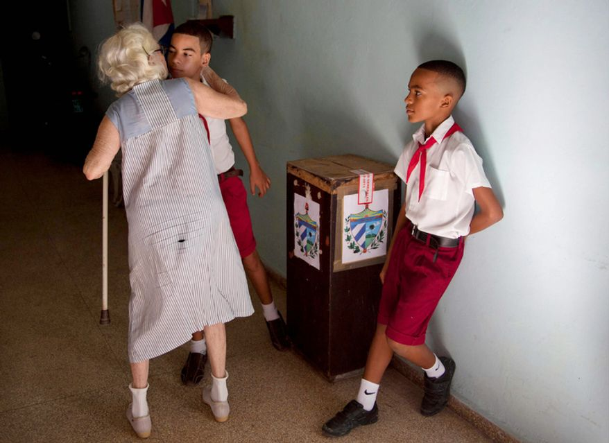 "A woman kisses a Cuban student after voting in municipal elections  in Havana Sunday Oct. 21, 2012.  Cuban school children known as ""pioneros"" are in all polling stations during elections overseeing the process.(AP Photo/Ramon Espinosa)"