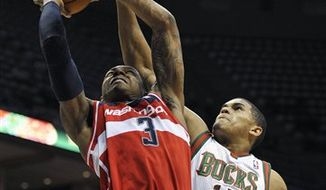 Washington Wizards' Bradley Beal (3) shoots over Milwaukee Bucks' Tobias Harris (15) during the first half of an NBA preseason basketball game, Saturday, Oct. 20, 2012, in Milwaukee. (AP Photo/Jim Prisching)