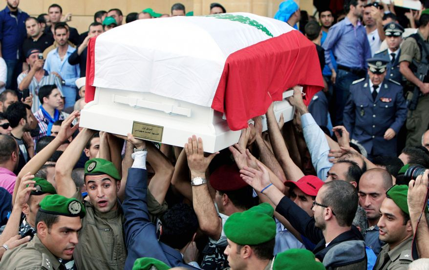 Lebanese honor guards carry coffins wrapped with Lebanese flags of Brig. Gen. Wissam al-Hassan and his bodyguard, Ahmad Sahyouni, who were assassinated on Friday by a car bomb, during their funeral procession at Martyrs' Square in Beirut, Lebanon, Sunday, Oct. 21, 2012. Thousands of Lebanese waving the national flag packed a central square in downtown Beirut Sunday for the funeral of a top intelligence official assassinated in a car bombing that many blame on the regime in neighboring Syria. (AP Photo/Bilal Hussein)