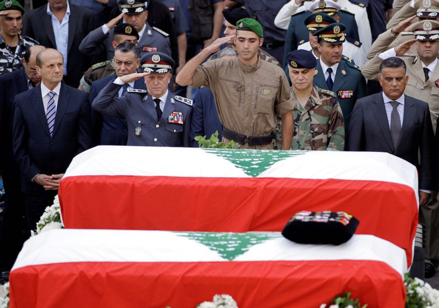 Lebanese police chief, Brig. Gen. Ashraf Rifi, second left, and a member of Lebanese police intelligence division unit, center, salute the two coffins wrapped with Lebanese flags of Brig. Gen. Wissam al-Hassan and his bodyguard Ahmad Sahyouni who were assassinated on Friday by a car bomb, during their funeral processions at the Lebanese police headquarters in Beirut, Lebanon, Sunday Oct. 21, 2012. Thousands of Lebanese waving the national flag packed a central square in downtown Beirut Sunday for the funeral of a top intelligence official assassinated in a car bombing that many blame on the regime in neighboring Syria. (AP Photo/Hussein Malla)