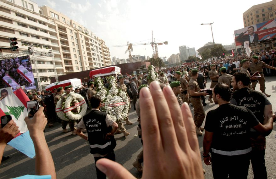 Mourners wave and take pictures as a Lebanese honor guard carries coffins wrapped with Lebanese flags of Brig. Gen. Wissam al-Hassan and his bodyguard, Ahmad Sahyouni, who were assassinated on Friday by a car bomb, during their funeral procession at Martyrs' Square in Beirut, Lebanon, Sunday, Oct. 21, 2012. Thousands of Lebanese waving the national flag packed a central square in downtown Beirut Sunday for the funeral of a top intelligence official assassinated in a car bombing that many blame on the regime in neighboring Syria.(AP Photo/Maya Alleruzzo)
