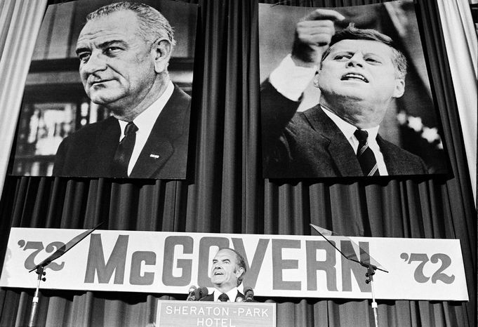 In this Aug. 9, 1972 file photo, with the pictures of former Democratic Presidents Kennedy and Johnson behind him, Sen. George McGovern, D-S.D., introduces Sargent Shriver as his new vice presidential running mate to the Democratic National Committee in Washington. A family spokesman says, McGovern, the Democrat who lost to President Richard Nixon in 1972 in a historic l