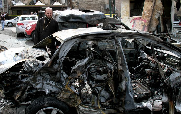 A Syrian looks at a damaged car at the site of a car bomb attack in the Bab Touma neighborhood, a popular shopping district largely inhabited by Syria's Christian minority, in Damas