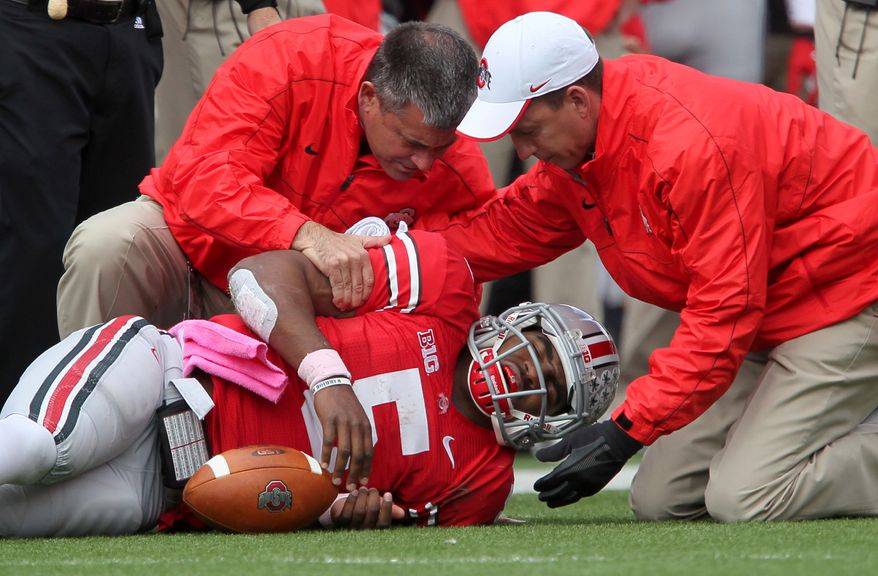 Ohio State Buckeyes quarterback Braxton Miller (5) grimaces in pain as he is helped by trainers after getting injured in the third quarter of an NCAA college football game against Purdue, Saturday, Oct. 20, 2012.  Miller did not return to the game.  (AP Photo/The Plain Dealer, Marvin Fong) MANDATORY CREDIT; NO SALES; ONLINE OUT; TV OUT