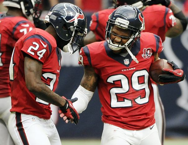 Houston Texans strong safety Glover Quin (29) celebrates his interception against the Baltimore Ravens with Johnathan Joseph (24) during the second quarter of an NFL football game, Sunday, Oct. 21, 2012, in Houston. (AP Photo/Dave Einsel)