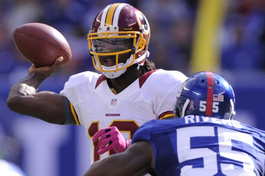 Washington Redskins quarterback Robert Griffin III (10) throws a first down pass in front of New York Giants outside linebacker Keith Rivers (55) during the third quarter at MetLife Stadium, East Rutherford, N.J., Oct. 21, 2012. (Preston Keres/Special to The Washington Times)