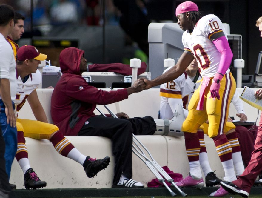 Washington Redskins tight end Fred Davis (83) shakes hands with quarterback Robert Griffin III (10) after being taken out of the game in the first half against the New York Giants at Metlife Stadium, East Rutherford, N.J., Oct. 21, 2012. Davis came out in the second half wearing a boot on his left leg. (Craig Bisacre/The Washington Times)