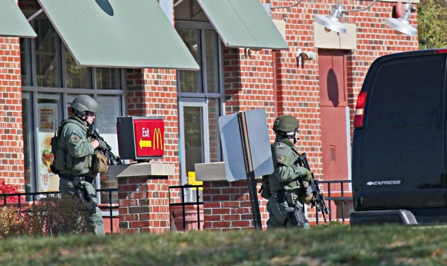 Tactical team members move past a McDonald's on the way to spa next door where, police say multiple people were wounded when someone opened fire, near the Brookfield Square Mall in Brookfield, Wis., Sunday, Oct. 21, 2012. Police launched a manhunt for a gunman they believe opened fire at the suburban Milwaukee spa, killing three people and wounding four before fleeing. (AP Photo/Milwaukee Journal-Sentinel, Michael Sears)