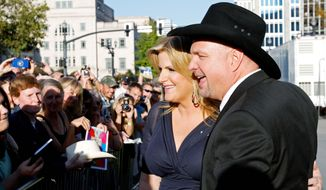 ** FILE ** Garth Brooks and his wife, Trisha Yearwood, greet fans outside the Country Music Hall of Fame in Nashville, Tenn., before his induction into the hall in this 2012 file photo. (Invision via Associated Press)