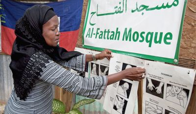 Darlene Derosier, 43, a Muslim convert since the 2010 earthquake in Haiti, posts a sign explaining Islamic cleansing rituals for prayer at the Al-Fattah Mosque in Gressier. The tradition of constant washing, she said, helps Muslims avoid cholera.