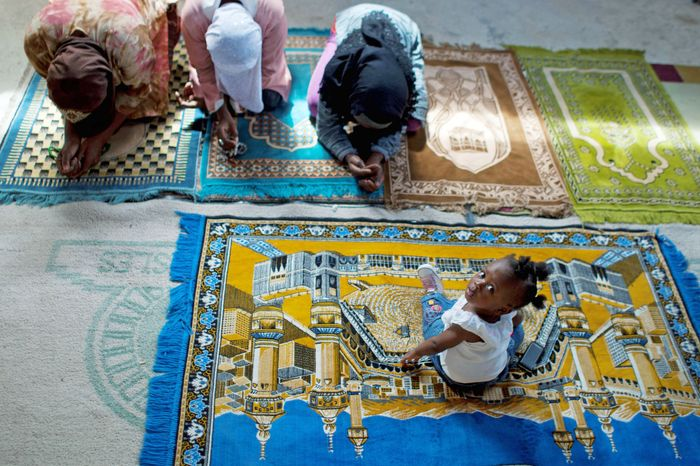 Christine Brazile sits on a prayer mat as relatives pray during a Friday prayer service last month at the Al-Fattah Mosque. Islam, a new religion in Haiti, is gaining adherents. Port au Pri