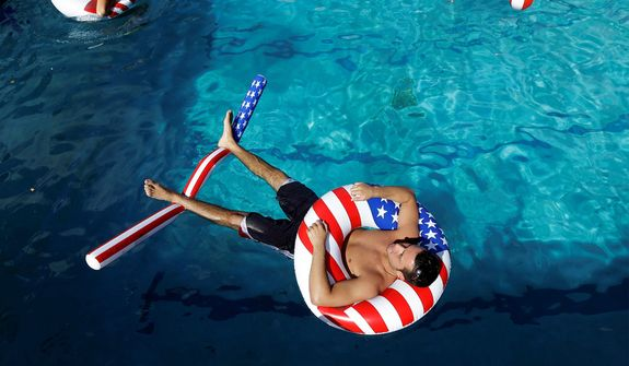 Lynn University student Matt Alleva uses patriotic tubes to float on the water during a pre-debate pool party on campus, Monday, Oct. 22, 2012, in Boca Raton, Florida. President Barack Obama and Republican presidential candidate and former Massachusetts Gov. Mitt Romney will hold their final debate at Lynn University Monday. (AP Photo/Eric Gay)