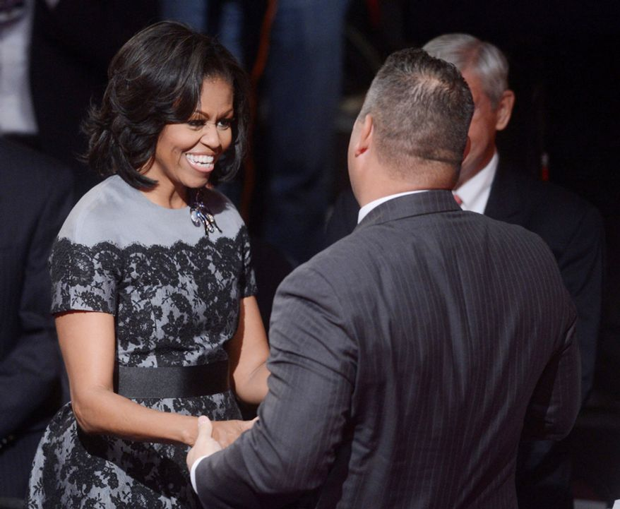 First lady Michelle Obama is greeted before the start of the third presidential debate at Lynn University, Monday, Oct. 22, 2012, in Boca Raton, Fla. (AP Photo/Pool-Michael Reynolds)