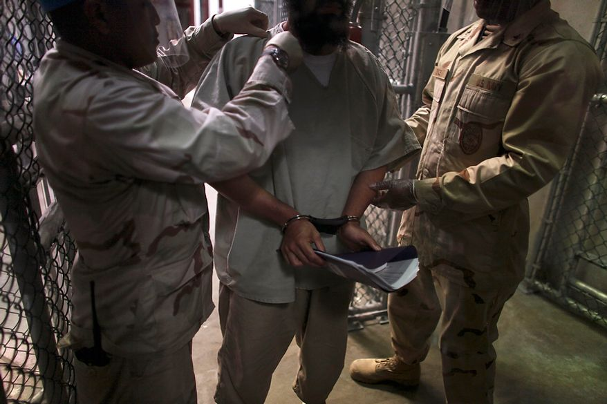 """In this photo, made through one way glass, reviewed by the U.S. military, a Guantanamo detainee is frisked before being transported by guards after attending a class in """"Life Skills,"""" inside Camp 6 high-security detention facility at Guantanamo Bay U.S. Naval Base, Cuba, Tuesday, March 30, 2010. The Obama Administration is pushing to close the Guantanamo detention facility, by  transferring, prosecuting, or releasing the remaining detainees. (AP Photo/Brennan Linsley)"""