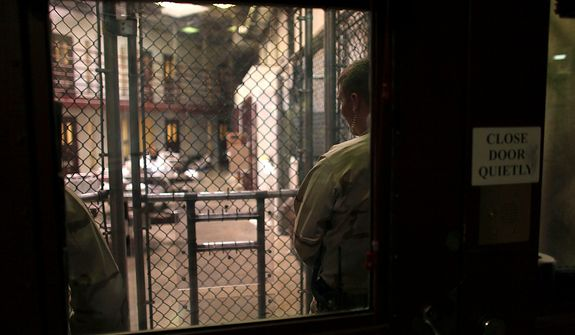 In this March 29, 2010 photo, reviewed by the U.S. military, photographed through one-way glass, Guantanamo guards keep watch over detainees inside a common area at Camp 6 high-security detention facility at Guantanamo Bay U.S. Naval Base, Cuba. The Obama Administration is pushing to close the Guantanamo detention facility, by  transferring, prosecuting, or releasing the remaining detainees. (AP Photo/Brennan Linsley)