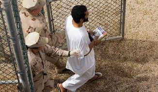Guards escort a Guantanamo detainee carrying a book at the Camp 4 detention facility's open-air common area at the U.S. naval base in Guantanamo Bay, Cuba, on Nov. 18, 2008. (AP Photo/Brennan Linsley) ** FILE **