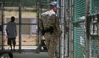 ** FILE ** In this May 31, 2009, pool file photo reviewed by the U.S. military and shot through a window, a guard wearing a protective face mask speaks with a detainee through a fence as another paces inside the exercise yard at Camp five detention facility on Guantanamo Bay U.S. Naval Base in Cuba. (AP Photo/Brennan Linsley, Pool)
